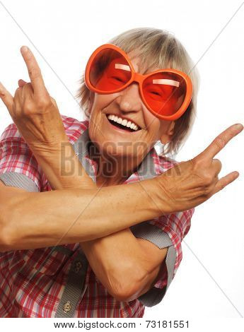 Senior woman wearing big sunglasses doing funky action isolated on white background