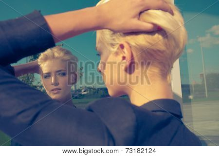 young blue eyes woman with trendy short blonde hair in black blazer look at own reflection in window outdoor shot