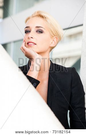 smiling young blue eyes woman with short blonde hair in elegant black blazer outdoor city portrait