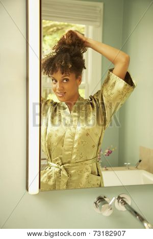African American woman putting up hair