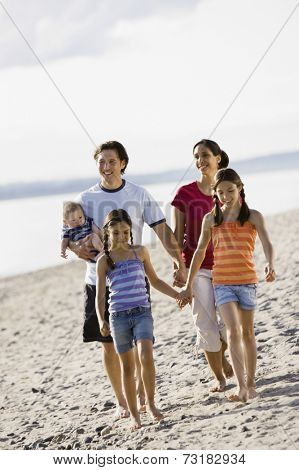 Multi-ethnic family walking on beach