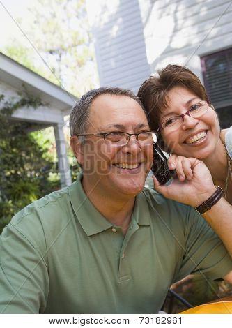 Hispanic couple listening to cell phone
