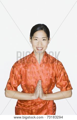 Asian woman bowing with hands pressed together