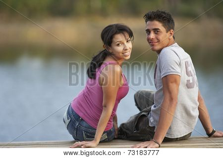 Multi-ethnic couple sitting on dock