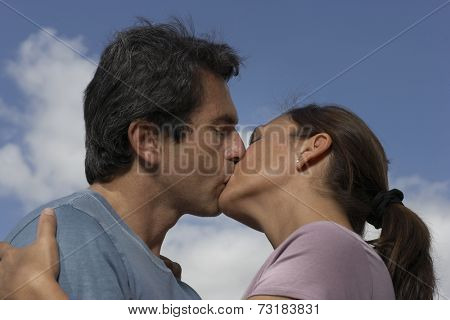 Low angle view of Hispanic couple kissing