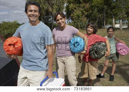 Hispanic family holding sleeping bags