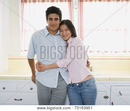 Multi-ethnic couple hugging in kitchen