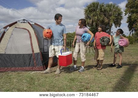 Hispanic family holding sleeping bags next to tent