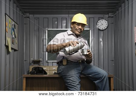 Senior African American male worker drinking coffee