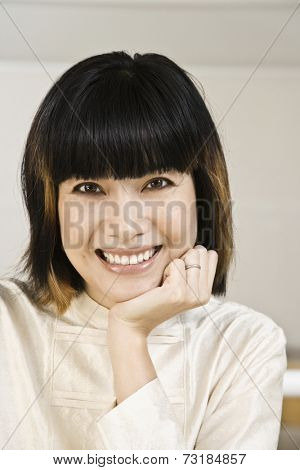Asian woman resting chin on hand