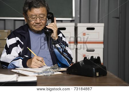 Senior Asian male worker talking on telephone