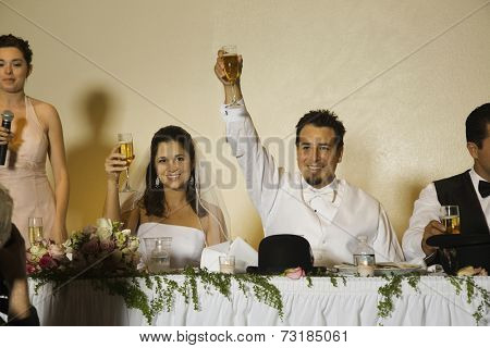 Hispanic newlyweds toasting with champagne