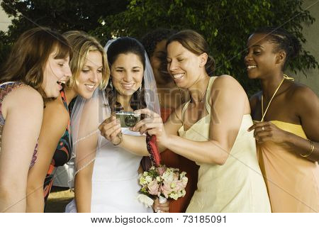 Hispanic bride and friends looking at camera