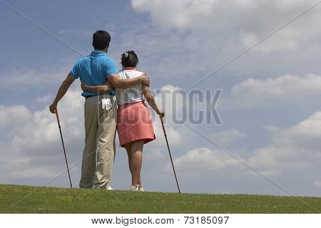 Hispanic couple hugging on golf course