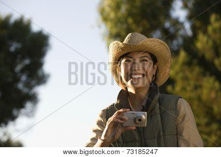 Asian woman holding camera