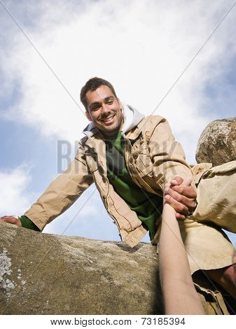 Pacific Islander man helping person climb