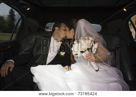 Hispanic newlyweds kissing in limousine