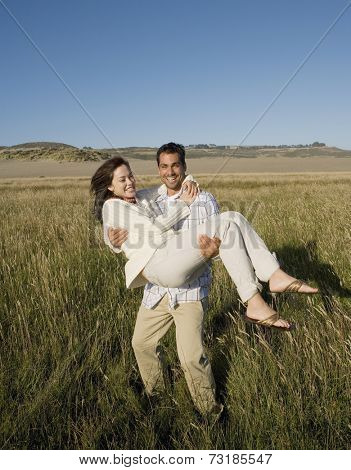 Pacific Islander man carrying girlfriend