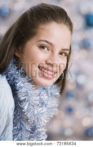 Hispanic teenaged girl wearing Christmas garland
