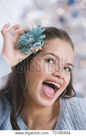 Hispanic teenaged girl holding bow in hair