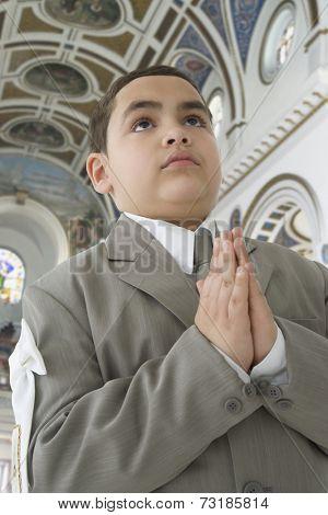 Hispanic boy praying in church