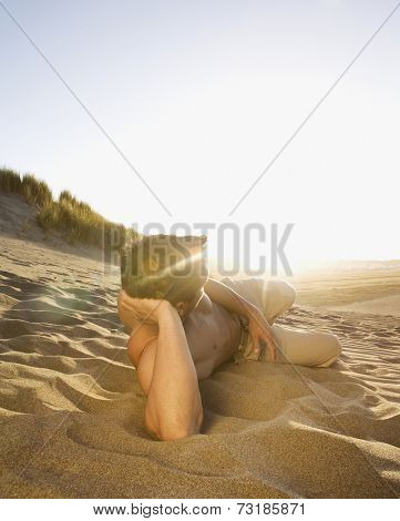 Pacific Islander man laying in sand