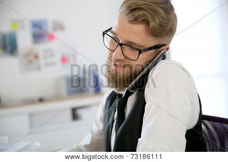 Young designer in office talking on phone