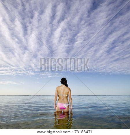 Pacific Islander woman standing in ocean