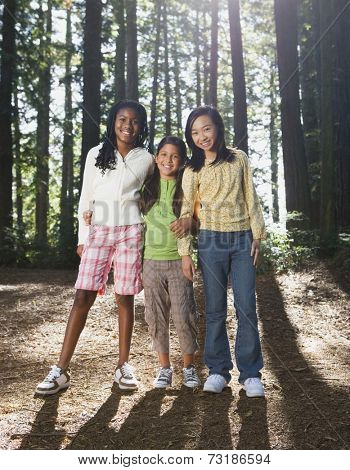Multi-ethnic girls standing in woods