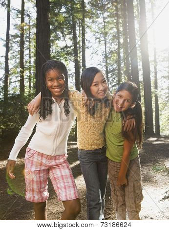 Multi-ethnic girls hugging in woods