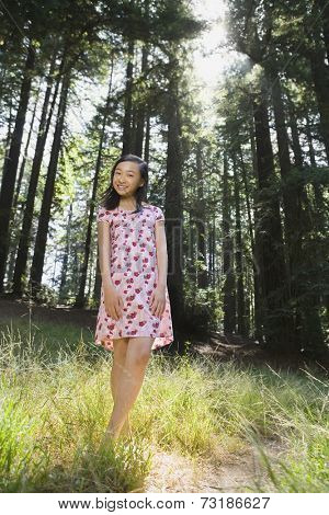 Asian girl standing in woods