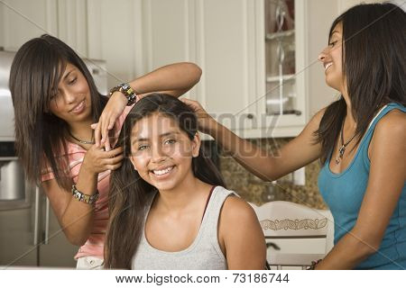 Hispanic teenaged girls fixing friend's hair