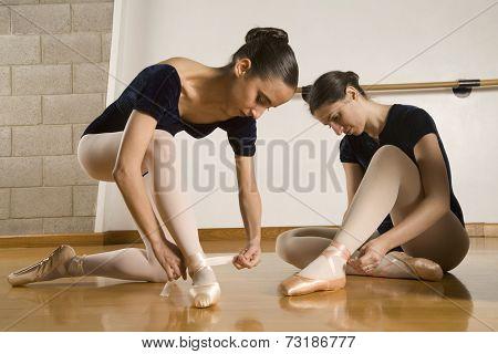 Hispanic female ballet dancers fastening shoes