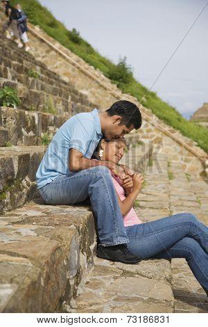 Hispanic couple sitting on stone steps, Oaxaca, Mexico