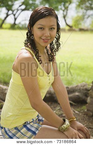 Hispanic teenaged girl with hands on knees