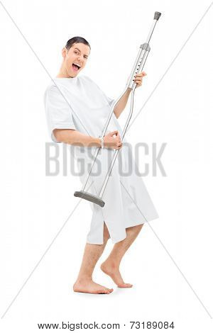Full length portrait of a silly patient playing on a crutch and dancing isolated on white background