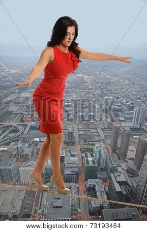 Young businesswoman walking on tightrope with city in background