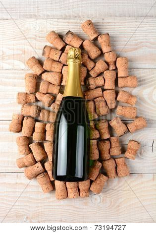 High angle shot of an champagne bottle laying on its side and surrounded by old used corks. Horizontal format on a rustic white wood background.