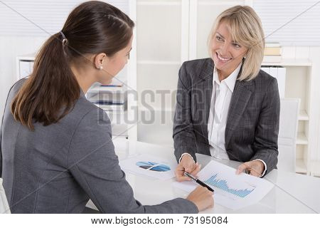 Two business woman sitting at desk: customer and adviser talking together.