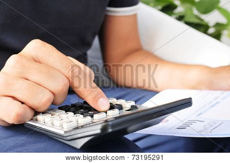 closeup of a young man checking a bill, a budget or a payroll with a calculator
