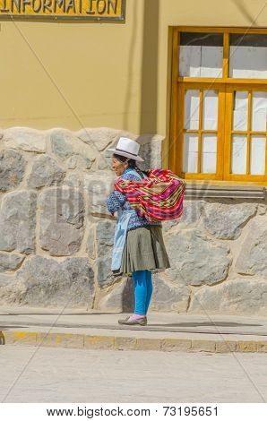OLLANTAYTAMBO, PERU, MAY 4, 2014 -  Local woman in traditional attire walks down the street