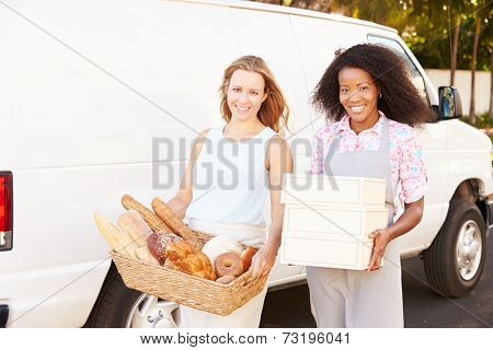 Female Bakers Unloading Bread And Cakes From Van