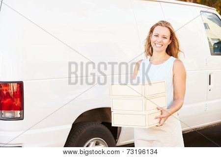 Female Baker Unloading Cakes From Van