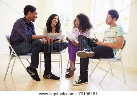 Group Of Business People Sitting On Chairs Having Meeting