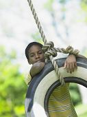 pic of tire swing  - Portrait of boy on tire swing - JPG