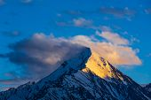 image of himachal pradesh  - Snowcapped summit top of mountain in Himalayas in clouds on sunset - JPG