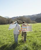 pic of lawn chair  - Couple carrying their lawn chairs across green meadow - JPG