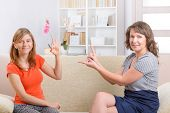 stock photo of deaf  - Smiling deaf woman learning sign language and talking with her teacher - JPG
