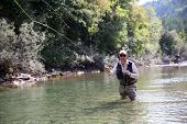 image of fly rod  - Closeup of fisherman fly fishing in freshwater river - JPG