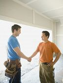 picture of friendship belt  - Male carpenters shaking hands inside construction site - JPG